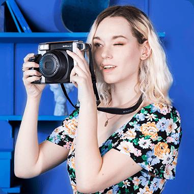 Une fille qui tient un appareil photo argentique